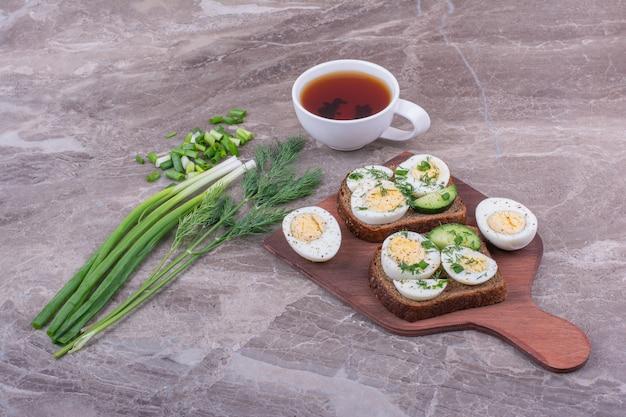 Toastbrood met gekookte eieren en kruiden geserveerd met een kopje thee.