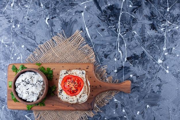 Toastbrood met zure room en gesneden tomaten op houten raad.
