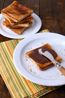 Toastbrood uitgespreid met chocolade op plaat met mes en servet op houten lijstachtergrond