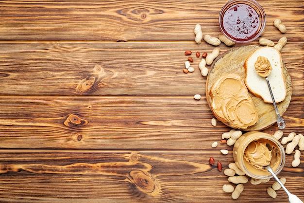 Toastsandwich met pindakaas. lepel en pot pindakaas, jam en pinda's voor het koken van ontbijt op een bruine houten achtergrond. plat leggen met plaats voor tekst.