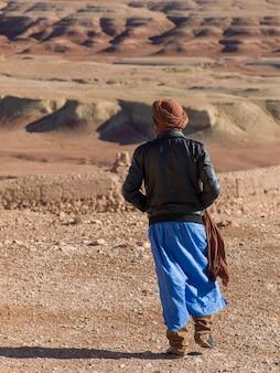 Toeareg man kijkt naar een uitzicht op de stad vanaf het terras van een fort, ait benhaddou, ouarzazate, souss-massa