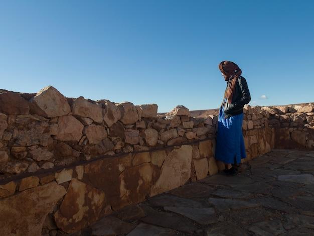 Toeareg man staat op het terras van een fort, ait benhaddou, ouarzazate, souss-massa-draa, marokko