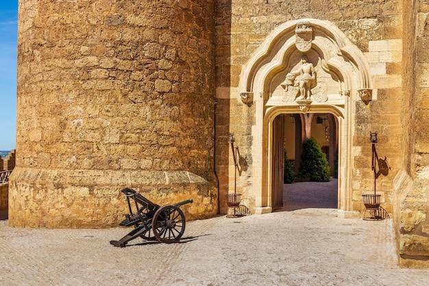 Toegang tot het kasteel van belmonte met toegangsdeur en oud kanon dat naar de deur wijst. castilla la mancha, spanje. europa.