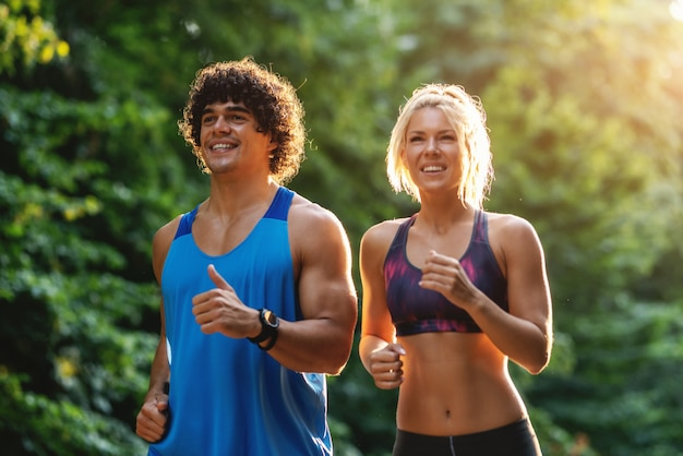 Toegewijd glimlachend paar dat in het bos op zonnige de zomerdag loopt. van je middel omhoog.