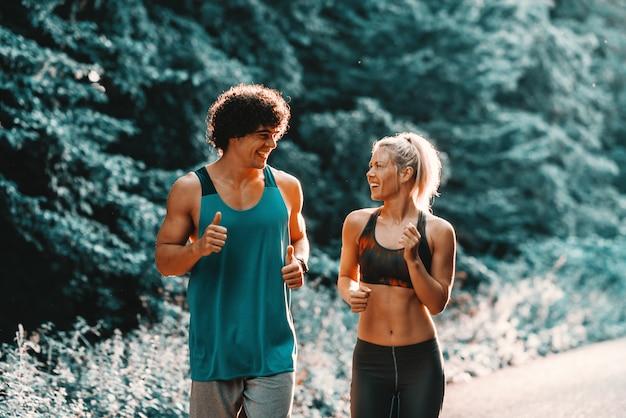 Toegewijd glimlachend paar dat in het bos op zonnige de zomerdag loopt.