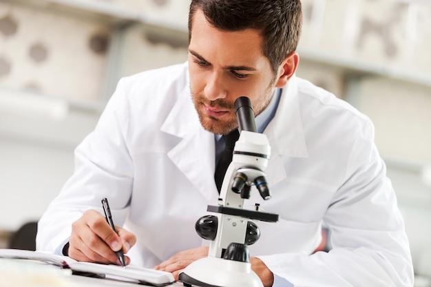 Toegewijd om de remedie te vinden. knappe jonge wetenschapper in wit uniform met behulp van microscoop en schrijven in notitieblok zittend op zijn werkplek