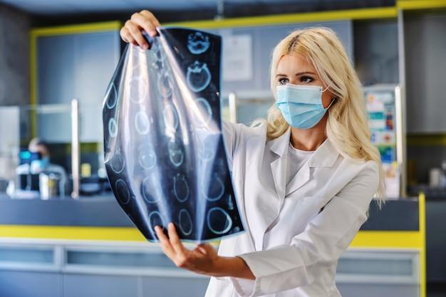 Toegewijde arts die een röntgenfoto van de hersenen van de patiënt vasthoudt en ernaar kijkt.