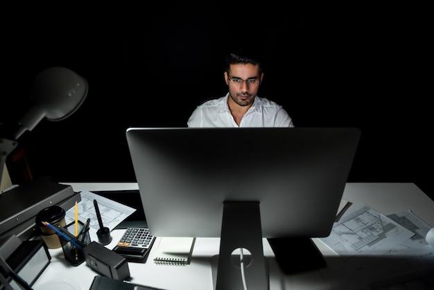 Toegewijde aziatische architect die zich concentreert op 's nachts achter de computer werken