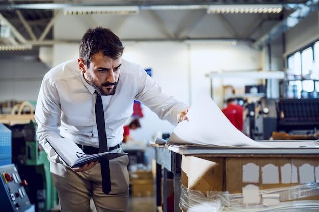 Toegewijde blanke bebaarde grafisch ingenieur in overhemd en das met notitieboekje en bladen kijken terwijl je in de drukkerij staat.