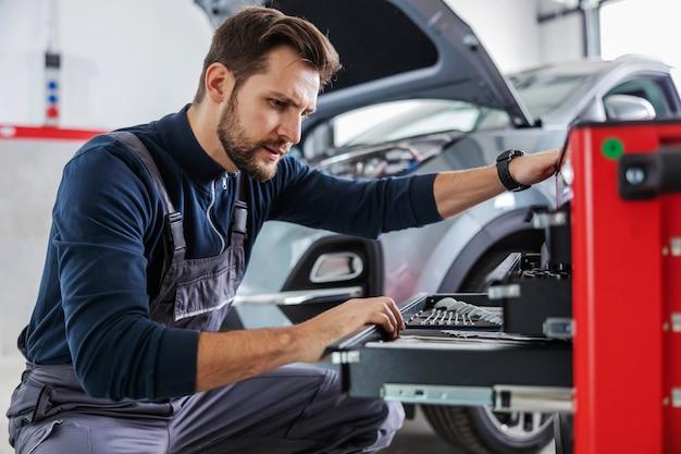Toegewijde ervaren monteur, gehurkt naast de doos met gereedschap en het kiezen van het juiste gereedschap voor het repareren van de auto. garage van auto salon interieur.