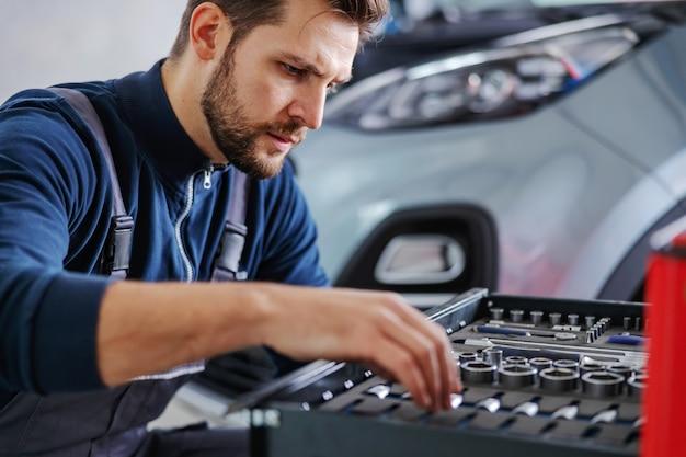 Toegewijde ervaren monteur hurkt naast een doos met gereedschap en kiest het juiste gereedschap om de auto te repareren. garage van auto salon interieur.