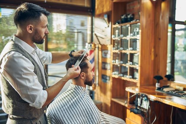 Toegewijde jonge kapper die zijn cliënt in de spiegel bekijkt terwijl hij zijn haar verzorgt en in model brengt