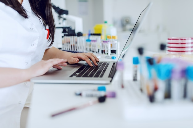 Toegewijde kaukasische vrouwelijke lab-assistent zit aan bureau en met behulp van laptop voor gegevensinvoer.