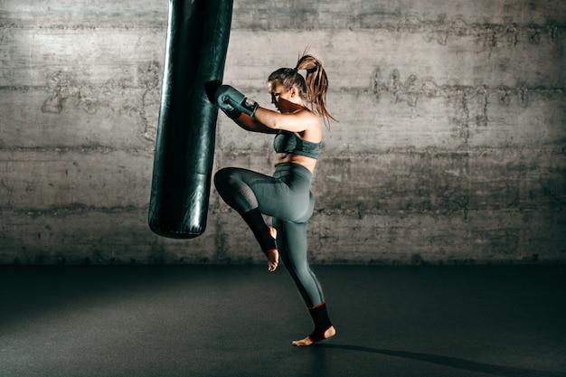 Toegewijde sterke brunette met paardenstaart, in sportkleding, op blote voeten en met bokshandschoenen