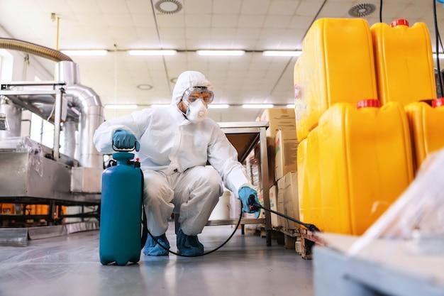 Toegewijde werknemer in beschermend wit uniform met rubberen handschoenen met sproeier met desinfectiemiddel en sproeien terwijl gehurkt in magazijn. corona-concept voorkomen.