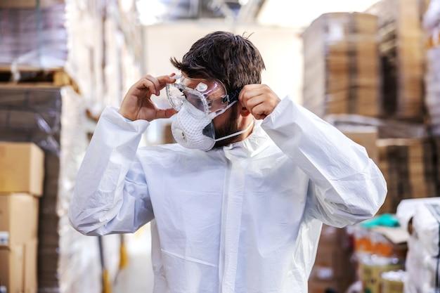 Toegewijde werknemer in wit steriel uniform permanent in magazijn en veiligheidsbril opzetten en voorbereiden om te steriliseren. corona uitbraak concept.