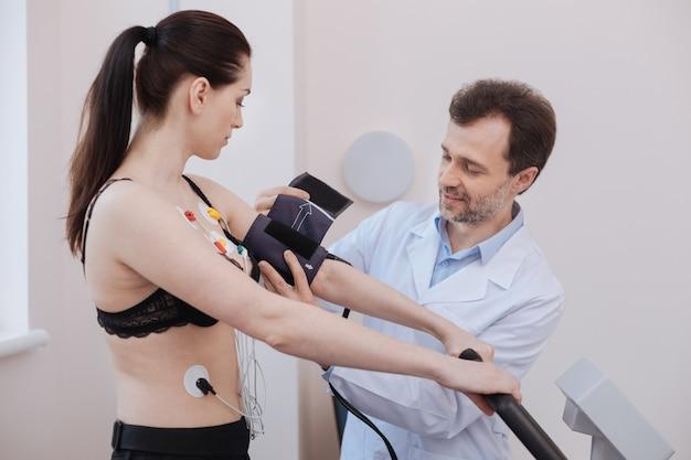 Toegewijde, zorgzame professionele cardioloog die ervoor zorgt dat hij alle systemen onder controle heeft voordat hij tests uitvoert op het cardiovasculaire systeem van zijn patiënt