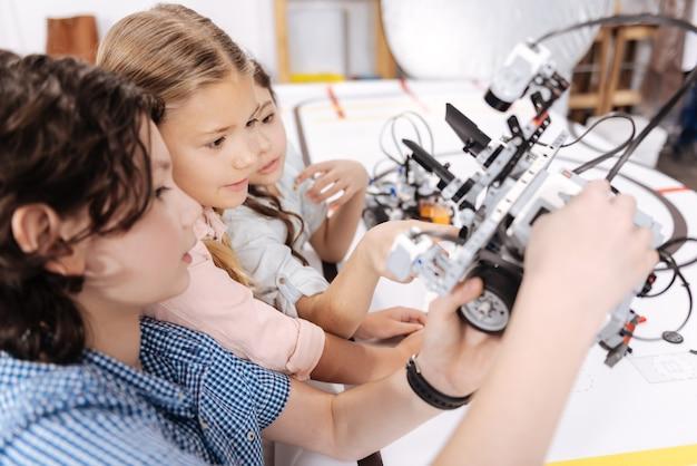 Toekomst in onze handen. geamuseerde bekwame opgetogen kinderen die op school zaten en met de robot speelden terwijl ze aan het technische project werkten