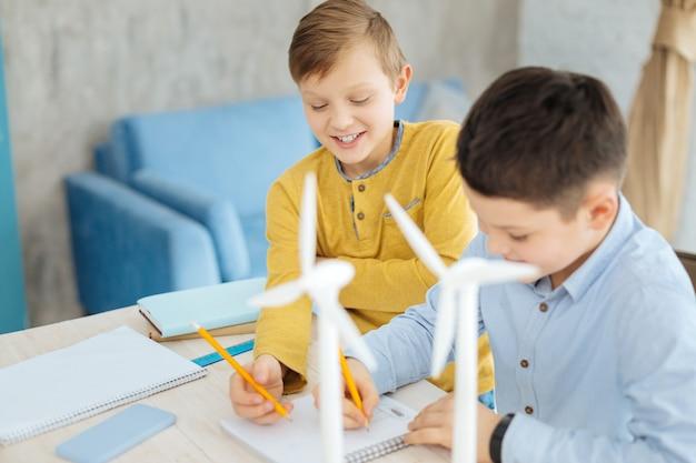 Toekomst van engineering. vrolijke pre-tienerjongens die samen aan tafel zitten en lachend de schetsen tekenen van windturbines die op de tafel staan