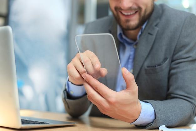 Toekomstig begrip. zakenman houdt futuristische transparante slimme telefoon.