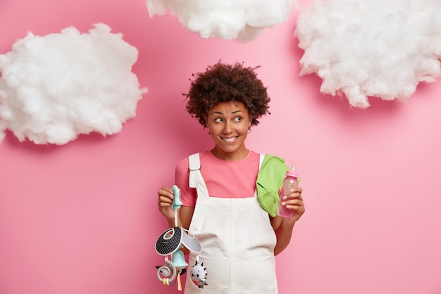 Toekomstig moederschap en zwangerschap concept. gelukkige aanstaande moeder houdt baby's mobiel en zuigfles vast, bereidt zich voor om moeder te worden, wacht op pasgeborene, geïsoleerd over roze muur, wolken erboven