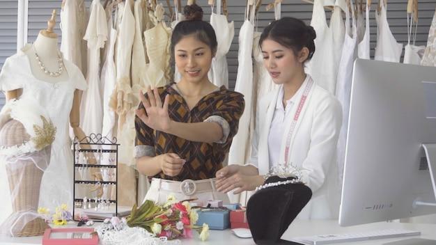 Toekomstige bruidklant in gesprek met de winkelier van de huwelijkswinkel om trouwjurk en accessoires te kopen voor haar aanstaande huwelijksceremonie