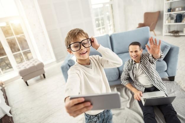 Toekomstige fotograaf. leuke, alerte blonde jongen die glimlacht en een grote bril draagt en selfies neemt terwijl zijn vader op de achtergrond zit