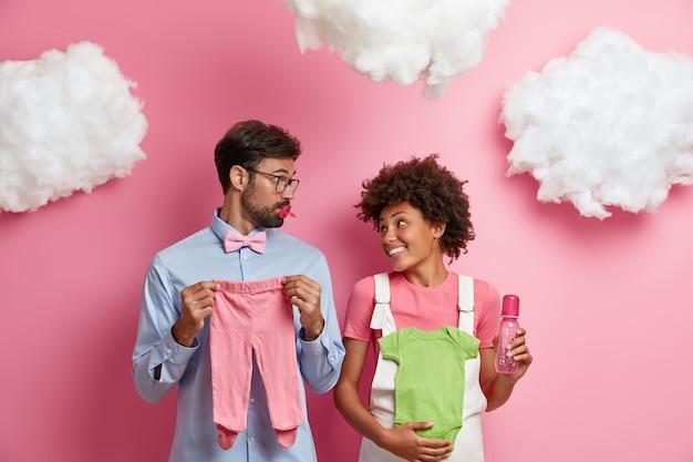 Toekomstige gelukkige ouders proberen het geslacht van de baby te raden, poseren met kinderschuifregelaars, hemd, fles voor voeding en tepel, verwachten geboorte van een kind, poseren tegen een roze muur met donzige witte wolken erboven