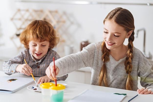 Toekomstige kunstenaars. leuke vrolijke creatieve broers en zussen die 's ochtends plezier hebben met schilderen met aquarellen terwijl ze genieten van hun weekend thuis