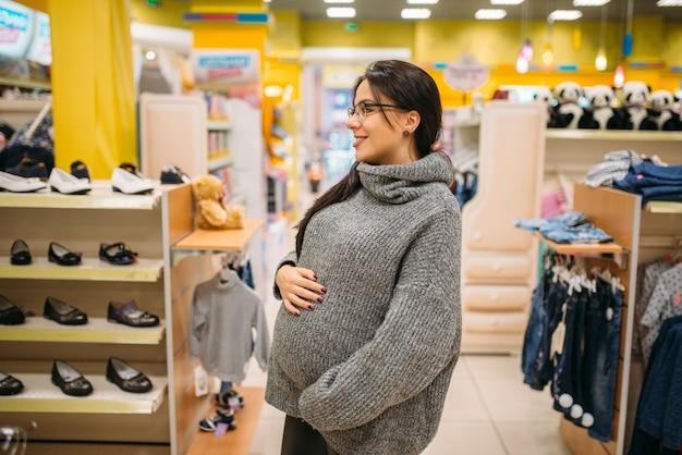 Toekomstige moeder in de winkel, schoenenafdeling