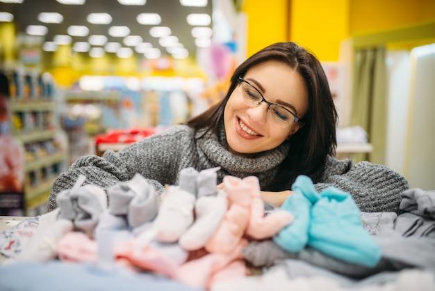 Toekomstige moeder in glazen koopt babykleertjes