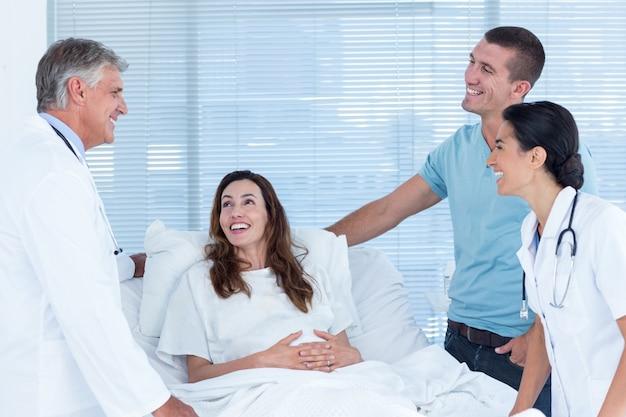 Toekomstige ouders praten met lachende artsen