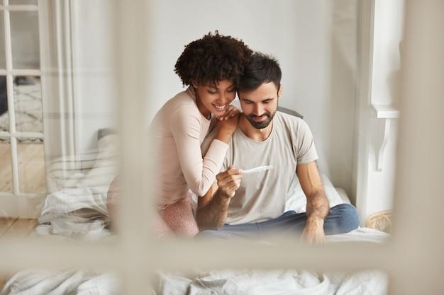 Toekomstige ouders van gelukkig gemengd ras kijken vreugdevol naar de zwangerschapstest, verheugen zich over positief nieuws over zwangerschap, zitten samen op bed tegen huiselijk interieur.