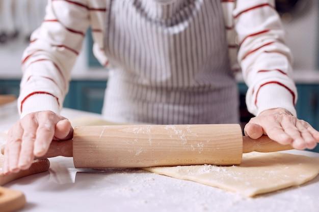 Toekomstige taart. de close-up van delicate handen van een oudere dame in een schort die een deegroller gebruikt om deeg uit te rollen tijdens het maken van een taart