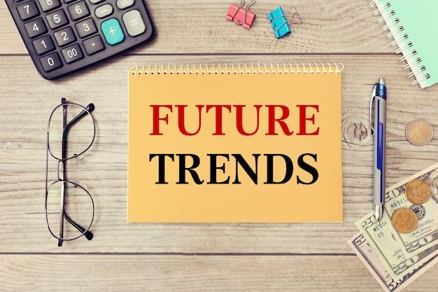 Toekomstige trends worden op een notitieblok op een bureau met kantoorbenodigdheden geschreven