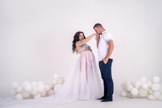 Toekomstige vader die de handen van zijn zwangere vrouw kust. mooi stel in studio
