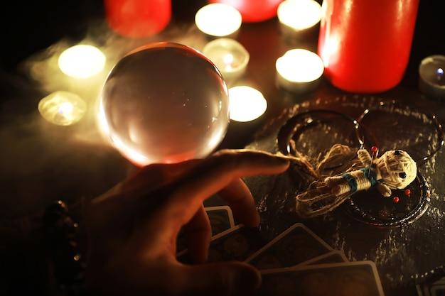 Toekomstige verteller. mystiek stilleven met voodoo-pop, de tarotkaarten, boeken, boze kaarsen en hekserijvoorwerpen. waarzeggerij.