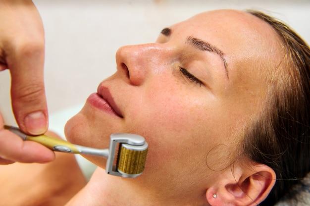 Toepassing van gouden maskers op het gezicht van het model. cosmetische ingrepen.