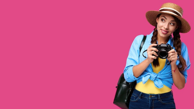Toerisme concept. gelukkige kaukasische vrouwentoerist die in de zomer vrijetijdskleding fotocamera houdt, die op roze achtergrond met exemplaarruimte wordt geïsoleerd