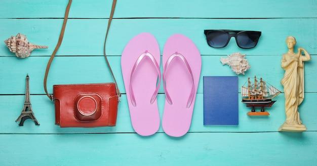 Toerisme concept. reiziger achtergrond. reis de wereld rond, platliggend. toeristische accessoires, souvenirs op een blauwe houten achtergrond.