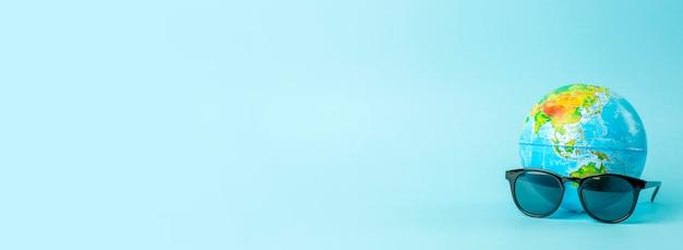 Toerisme, ecologie, vakantie en globalisme concept. bol in zonnebril op een blauwe banner als achtergrond. minimale advertentie