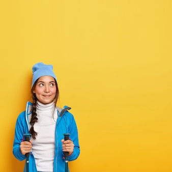 Toerisme en kamperen concept. dromerige brunette vrouw gebruikt wandelstokken, kijkt naar boven, geniet van buitenactiviteiten, kijkt bedachtzaam naar boven, draagt blauwe jas en hoed, kopie ruimte op gele muur.