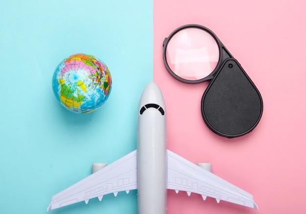 Toerisme en reizen concept. beeldje van wereldbol, vergrootglas en passagiersvliegtuig op roze blauwe pastelkleurige muur bovenaanzicht. plat leggen