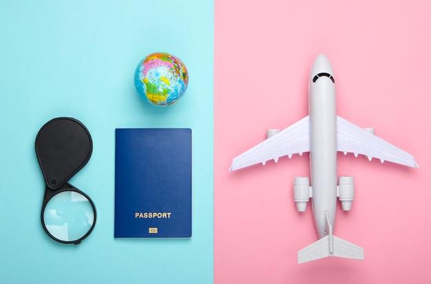 Toerisme en reizen concept. emigratie. beeldje van wereldbol, paspoort, vergrootglas en passagiersvliegtuig op roze blauwe pastelkleurige muur bovenaanzicht. plat leggen