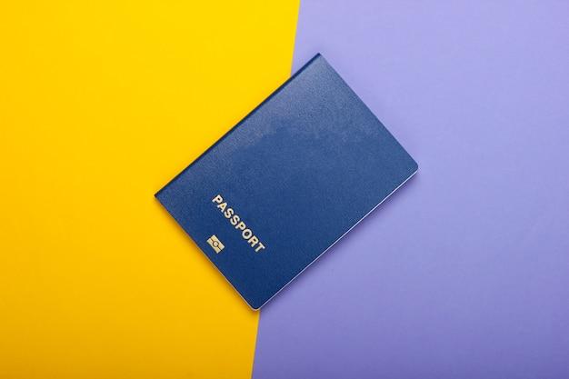 Toerisme en reizen concept. emigratie. paspoort op paars gele muur bovenaanzicht. plat leggen