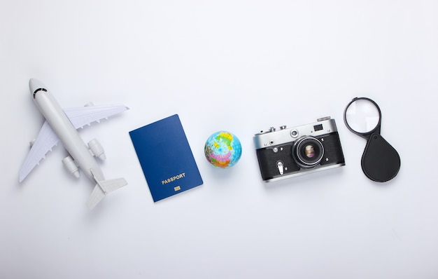 Toerisme en reizen concept. globe, camera, paspoort, passagiersvliegtuigbeeldje op witte muur bovenaanzicht. plat leggen