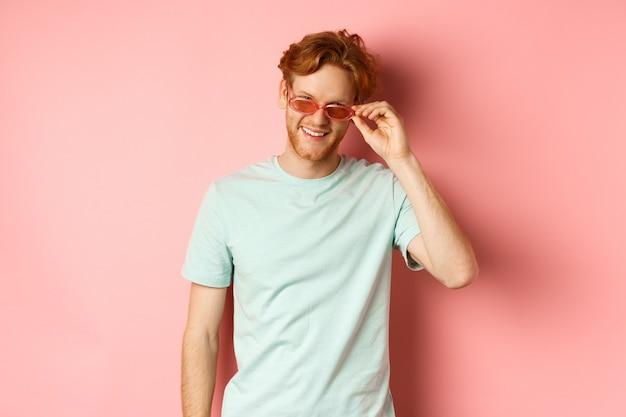 Toerisme en vakantie concept. ontspannen jonge man met rood haar, staande in zonnebril en t-shirt en glimlachend tevreden, staande op roze achtergrond.