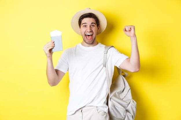 Toerisme en vakantie. man voelt zich gelukkig over zomervakantie, houdt paspoort vast met vliegtickets en rugzak, steekt handen omhoog in vieringsgebaar, gele achtergrond