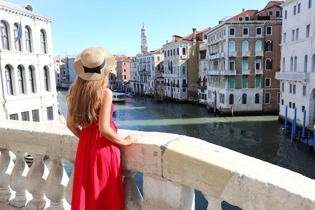 Toerisme in venetië. achteraanzicht van mooie jonge vrouw in rode jurk genieten van uitzicht op canal grande vanaf de rialtobrug in venetië, italië.