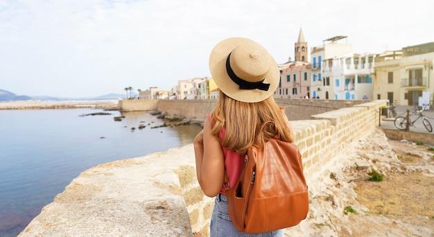 Toerisme op sardinië. panoramisch spandoekmening van jonge vrouw met hoed en rugzak in de oude stad van alghero, sardinië, italië.